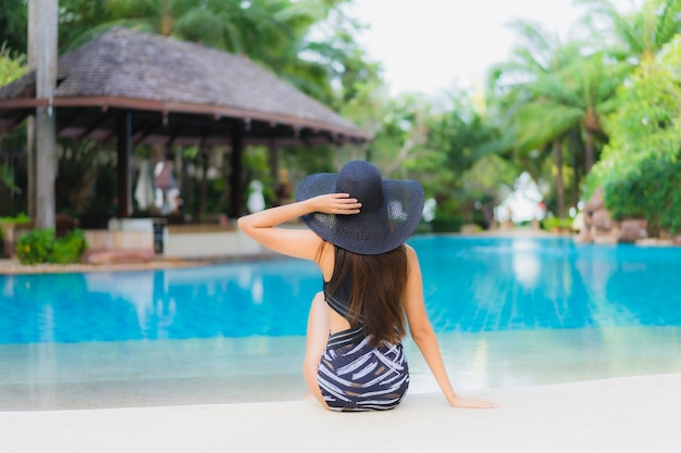 Улыбка красивых молодых азиатских женщин портрета счастливая ослабляет вокруг бассейна Бесплатные Фотографии