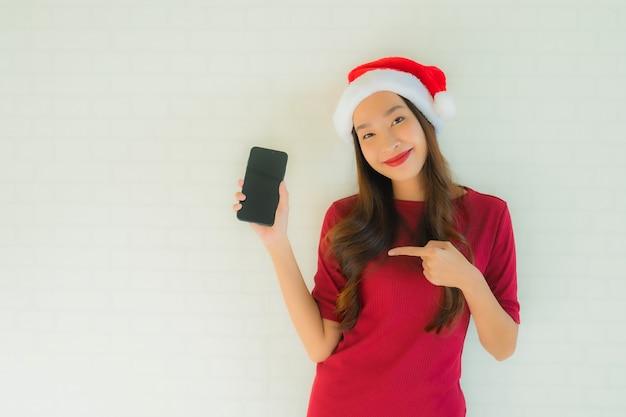 肖像画の美しい若いアジア女性は携帯電話でサンタのクリスマス帽子をかぶる 無料写真