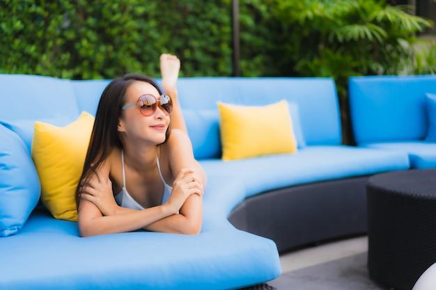 Улыбка красивой молодой азиатской женщины портрета счастливая ослабляет вокруг открытого бассейна Бесплатные Фотографии