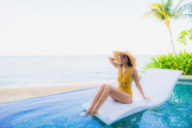 Улыбка красивых молодых азиатских женщин портрета счастливая ослабляет вокруг открытого бассейна Бесплатные Фотографии
