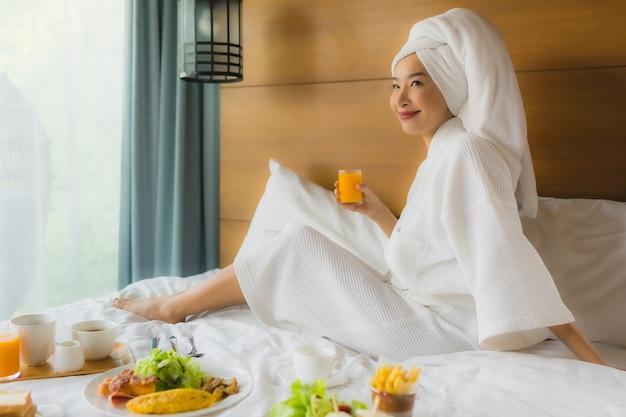 寝室で朝食とベッドの上の肖像若いアジア女性 無料写真