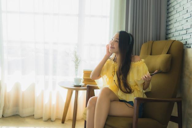 肖像若いアジア女性が椅子に座る携帯電話のコーヒーと本で音楽を聴く 無料写真