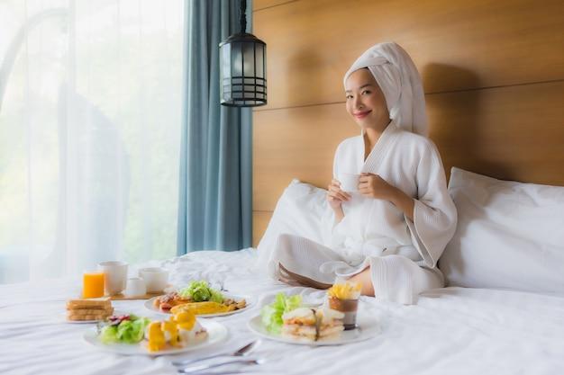 Портрет молодой азиатской женщины на кровати с завтраком в спальне Бесплатные Фотографии