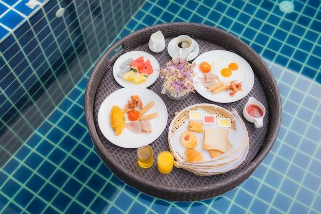 プールに浮かぶ朝食セット 無料写真