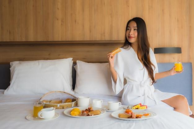 Азиатская женщина, наслаждаясь с завтраком на кровати Бесплатные Фотографии