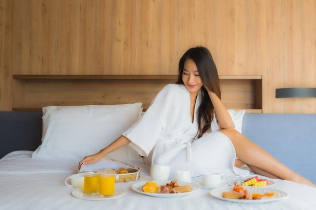 アジアの女性がベッドで朝食を楽しんで 無料写真