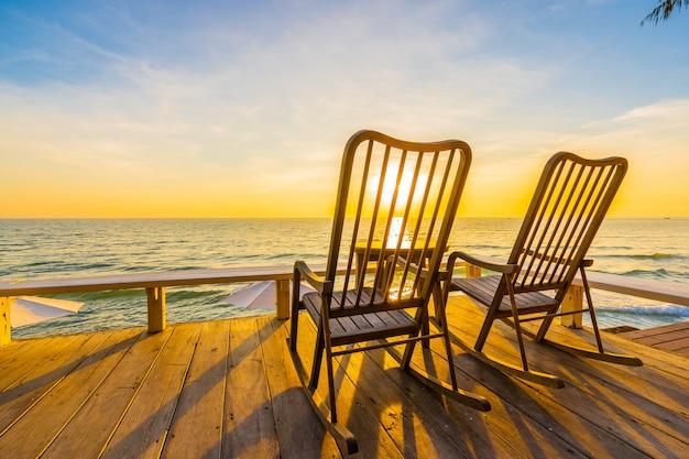 Пустой деревянный стул и стол на открытом патио с прекрасным тропическим пляжем и морем Бесплатные Фотографии