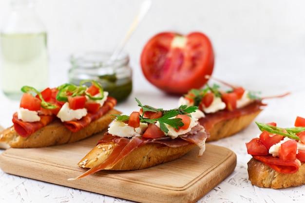 イタリアの前菜 - トマト、チリ、ソーセージ、木の板にチーズのブルスケッタ Premium写真