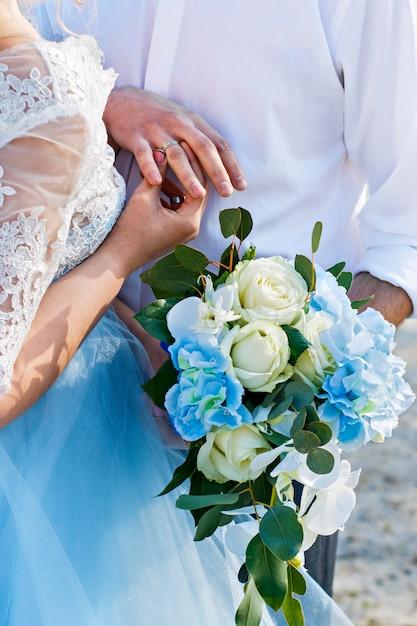 新婚夫婦はリングを着ます。結婚式。花嫁のブーケ指輪を新郎新婦。 Premium写真