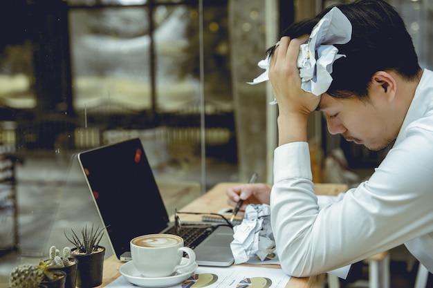 青年実業家はストレスで紙を粉砕しました。 Premium写真
