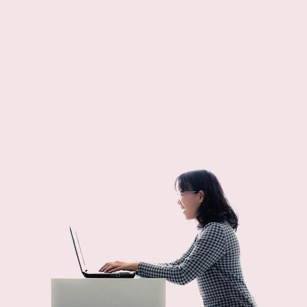 眼鏡をかけているアジアの女の子ノートパソコンを使用しながら彼女は楽しんでいます。 Premium写真
