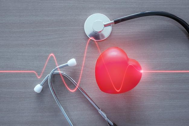 輝く赤いハートの波と聴診器と赤いハート。 Premium写真