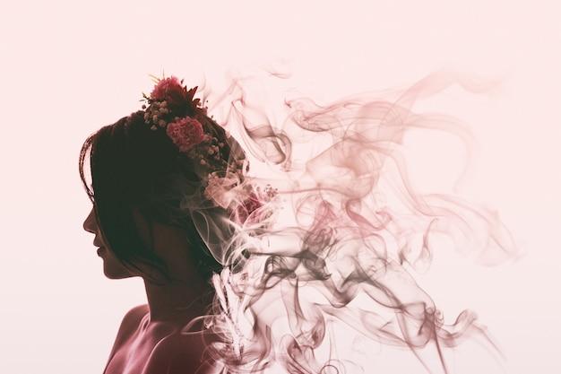 アジアの女の子は美しく、花の冠で魅力的です。彼女は蒸発して香水の煙になります。フレアライトスタイル。 Premium写真