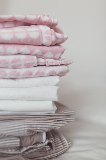 清潔でアイロンをかけたリネンの積み重ねがベッドの上にあります Premium写真