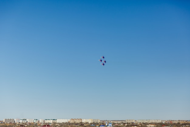 Квадратное формирование группы из четырех российских военных самолетов-истребителей, летящих высоко в синем небе Premium Фотографии