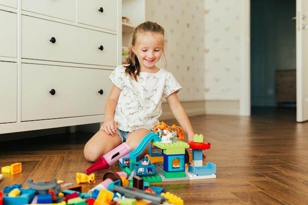 カラフルなおもちゃのブロックで遊ぶ少女。幼児向けの教育的で創造的なおもちゃとゲーム。子供の部屋での遊び時間と混乱 Premium写真