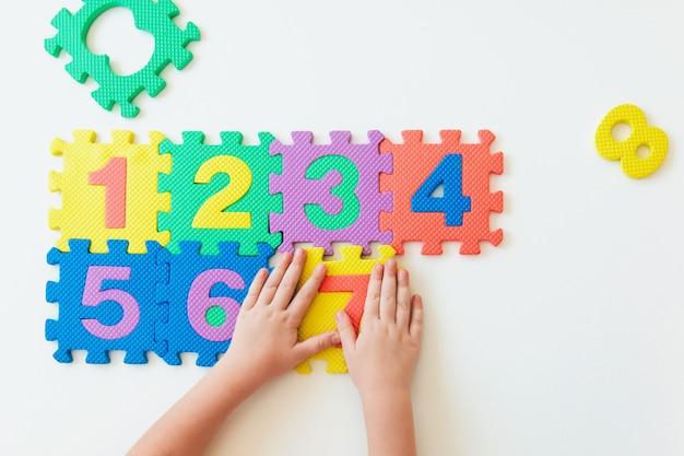 数字で遊ぶ子供の手、簡単な乗算を学ぶ Premium写真