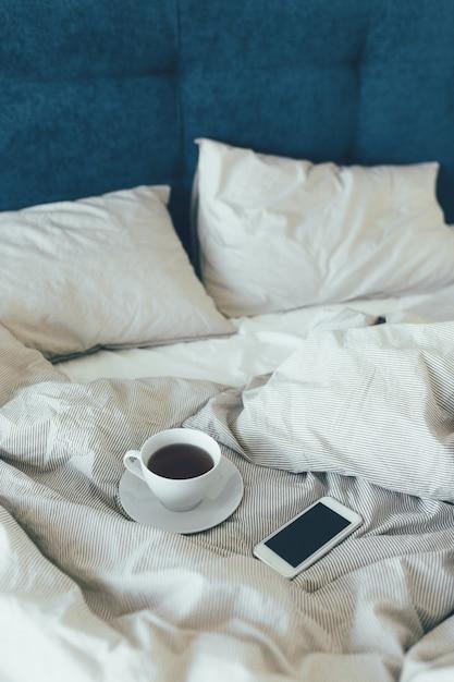 美容室に白い枕とベッドシーツでベッドメイドアップ。朝の朝食、紅茶。 Premium写真