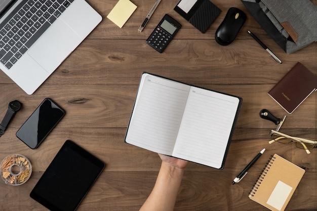 テーブルフラットのオフィスアクセサリーと空のノートブックリストに鉛筆を持っている手を置く Premium写真