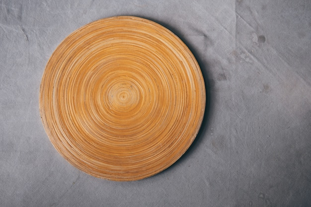 汚れの背景を持つ灰色のテーブルクロスを持つテーブルに空白の木製まな板。 Premium写真
