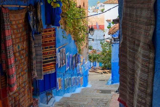 Традиционные ковры на синей улице шефшауэн в марокко Premium Фотографии
