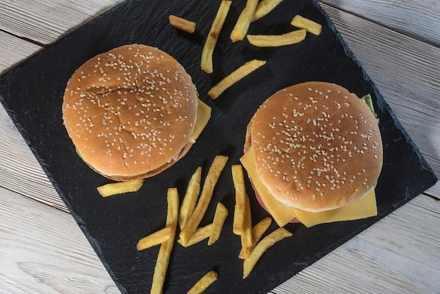 Два чизбургера на кунжутных булочках с сочными говяжьими котлетами с картофелем фри на черном сланце. Premium Фотографии