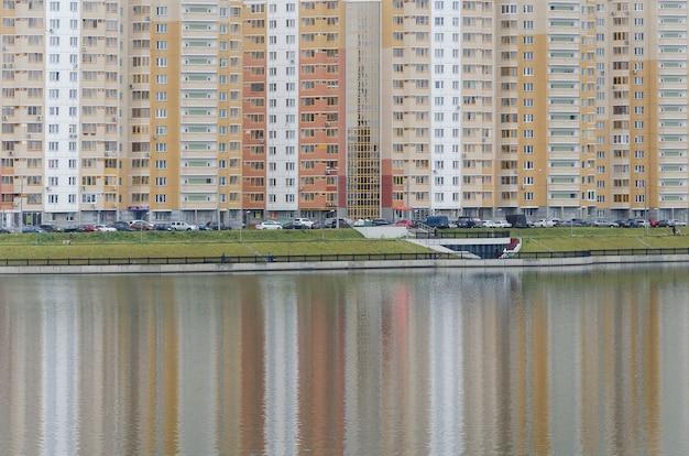 池のモスクワの新しい地区のマルチカラーハウスのリズミカルな反射。カラーバランス Premium写真