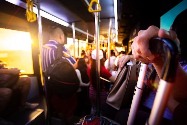 Туристический упаковщик держит свой багаж и мобильный телефон в автобусе для перевозки от терминала аэропорта до самолета. Premium Фотографии