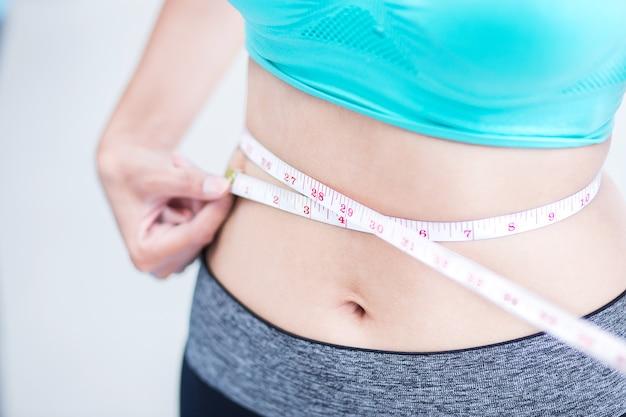 スリムスポーツ女性は、測定テープで腰を測定する Premium写真