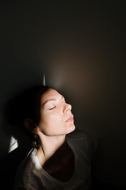 Девушка сидя самостоятельно в кармане солнечного света в темной комнате. концепция психического здоровья Premium Фотографии