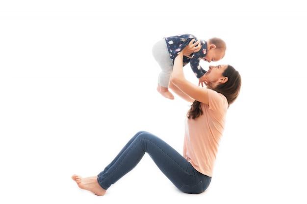 母親と赤ちゃんの体操、白い背景で隔離のヨガの練習 Premium写真