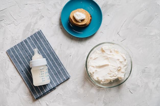 パンケーキとカッテージチーズのトップビュー健康食品とガラス板で自家製クリームチーズのボウル Premium写真