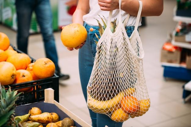 Женщина с сетчатой сумкой, полной свежих овощей, покупки в магазине, ноль отходов концепции Premium Фотографии