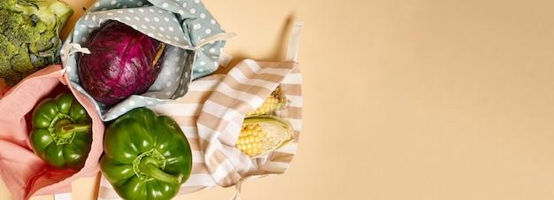 野菜が入った食料品用の布製コットンショッピングバッグ。ベージュ色の背景。プラスチックなし Premium写真