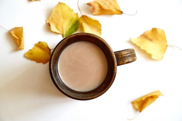 白のコーヒーまたは紅茶のカップと紅葉 Premium写真