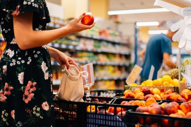 Женщина выбирает фрукты и овощи продовольственный рынок. многоразовая сумка для покупок. ноль отходов Premium Фотографии
