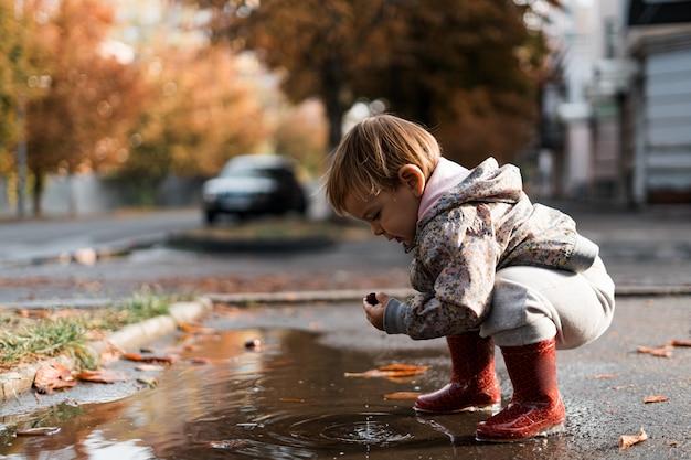 雨上がりの水たまりで遊んで赤い長靴の少女 Premium写真