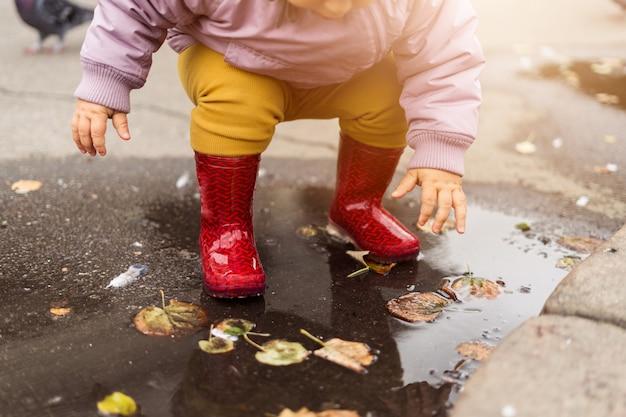 水たまり、鳥と街の広場で遊ぶ小さな男の子。ハト。秋の子供時代 Premium写真