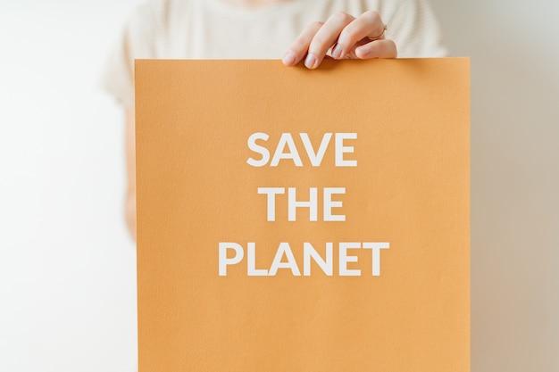 地球を救う-地球の緑の未来への抗議の生態サイン。女性持株紙 Premium写真