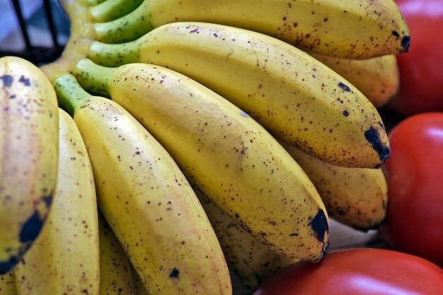 Банановый букет в корзине с фруктами с белым оборкой Premium Фотографии