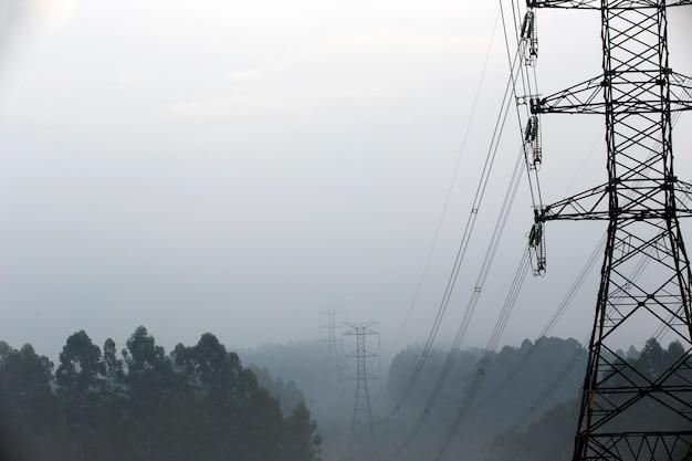 霧の中の電気送電の塔 Premium写真