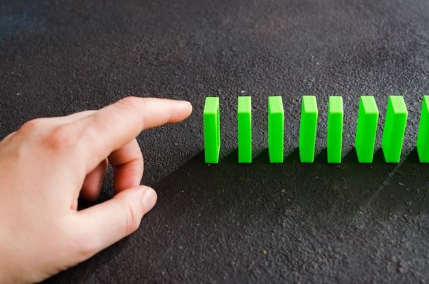連鎖反応を引き起こすためにドミノの部分を押す準備ができている手。 Premium写真
