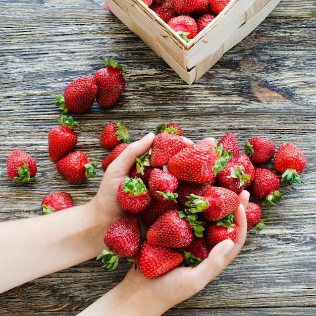 女性の手は新鮮な熟したイチゴの一握りを握る Premium写真