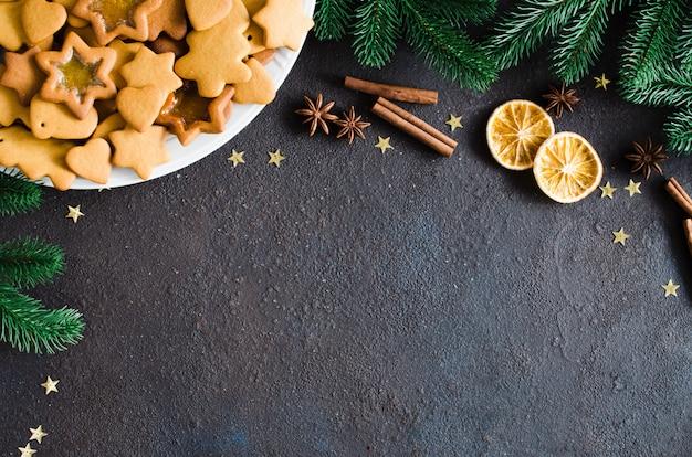焼きたてのクリスマスジンジャーブレッド、スパイス、モミの枝と料理の背景。 Premium写真