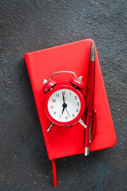 目覚まし時計、メモ帳、ペン Premium写真