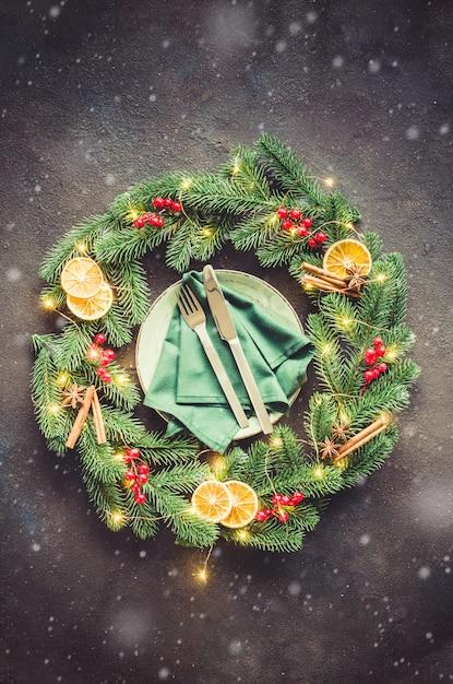 Праздничная сервировка стола с рождественскими украшениями в виде рождественского венка Premium Фотографии