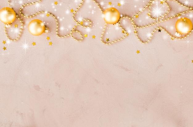 ゴールデンクリスマスの背景。装飾的なボールと星のビーズ。 Premium写真