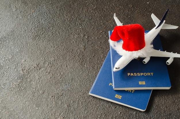 Игрушечный самолет с паспортами и шляпу санта-клауса. Premium Фотографии