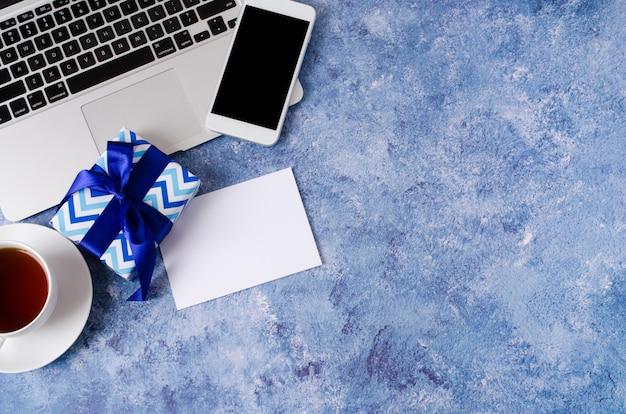青いギフトボックス、オフィスの机、ラップトップ、青い背景にお茶のカップに黒い空白の画面を持つスマートフォン。 Premium写真