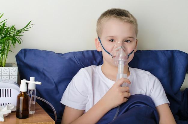 Больной мальчик дышит через небулайзер Premium Фотографии